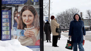 A woman carries shopping bags as she passes a poster informing people about the adoption of the euro in Parnu