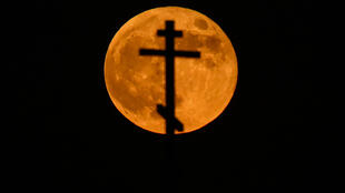 La superluna roja, vista detrás de una cruz de una iglesia ortodoxa en el sur de Rusia, el 26 de mayo de 2021