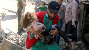 Un membre de la Défense civile évacue un enfant qui a survécu sous les décombres d'un site touché par des frappes aériennes à Alep en Syrie, le 28 avril 2016.