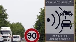 Cars drive past a roadside traffic speed radar placard in Saint Jean d'Illac near Bordeaux, southwestern France, May 12, 2011.
