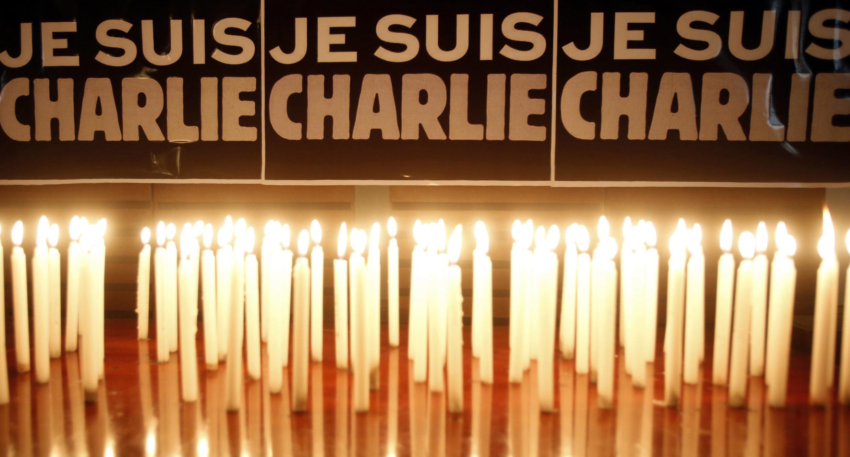 """Nến thắp sáng trước biểu ngữ """"Tôi là Charlie"""" (Je suis Charlie). Ảnh chụp nhân phút tưởng niệm nạn nhân vụ khủng bố tại báo Charlie Hebdo ở Paris, tổ chức tại Đại sứ quán Pháp ở Hà Nội hôm 08/01/2015."""