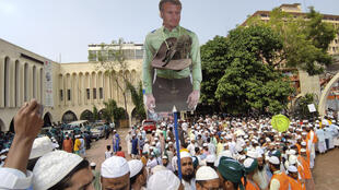 Supporters of Islami Andolan Bangladesh, an Islamist political party, carry a cutout of French President Emmanuel Macron with a garland of footwear around it as they protest against the publishing of caricatures of the Prophet Muhammad they deem blasphemous, in Dhaka, Bangladesh, Tuesday, Oct. 27, 2020. Muslims in the Middle East and beyond on Monday called for boycotts of French products and for protests over the caricatures, but Macron has vowed his country will not back down from its secular ideals and defense of free speech.