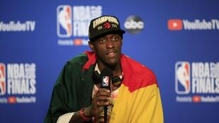Pascal Siakam, en conférence de presse, avec le drapeau du Cameroun sur les épaules et la casquette de champion NBA, après le sacre des Raptors de Toronto.