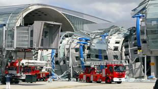 Emergency services work at the collapsed terminal building at Roissy airport, outside of Paris, 23 May 2004.