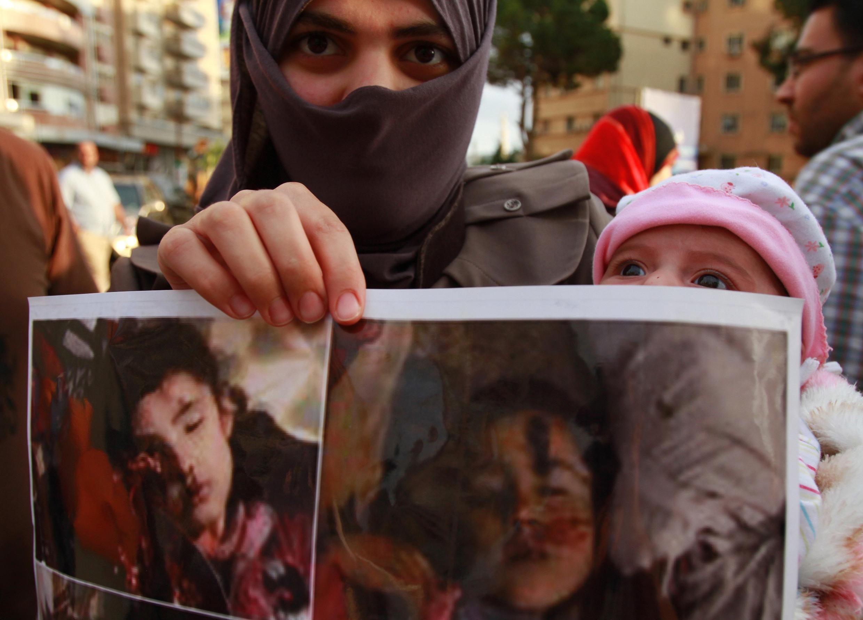 Mulher mostra a foto de duas crianças mortas durante os bombardeios a Hula.