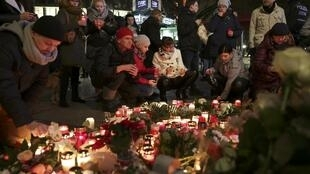 Candles burn at a Christmas market at Breitscheidplatz in Berlin, Germany, to commemorate the 12 victims of Monday's terror attack