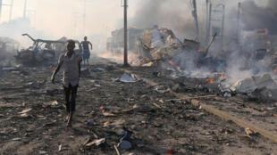 Des civils évacuant le lieu de l'attentat, le 14 octobre 2017 à Mogadiscio en Somalie.