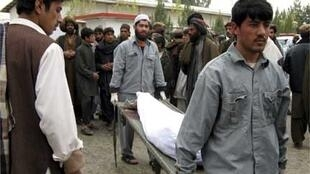 Hospital workers carry the body of a man killed in the Lashkar Gah blast