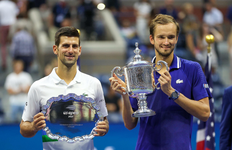 Daniil Medvedev (derecha) alza su trofeo de ganador del Abierto de Estados Unidos junto a Novak Djokovic.