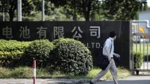 一名男子路经位于上海的美国江森自控电池工厂门前(2011年9月15日)