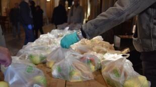 Eglise Sainte-Ambroise, le 24 mars. Première journée de distribution alimentaire. On compte les sacs restants.