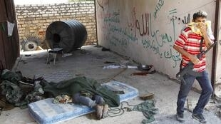 A rebel fighter walks near the bodies of fellow rebels at the Khamis 32 military encampment in southern Tripoli