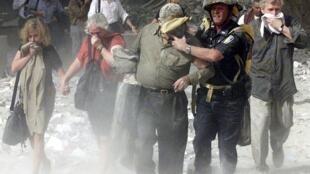 Un groupe escorté par un pompier est éloigné du World Trade Center à New York, le 11 septembre 2001.