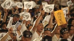 在台湾总统府前示威的人士手持绘有流血眼睛的牌子 2013 6 3