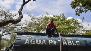 Un hombre llena un camión con agua potable para ser distribuido en hospitales y barrios, el 13 de marzo de 2019.