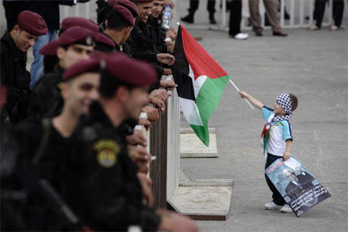 A Palestinian boy holds a flag out to Palestinian security force members in Ramallah