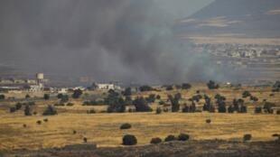 De la fumée s'élève de la partie syrienne du Golan, vue du côté israélien, le 24 juin 2016.