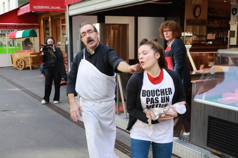 Un carnicero echa de su negocio a una militante anti-especista y vegana que carga un lechón muerto durante una protesta en París, el 22 de septiembre de 2018.