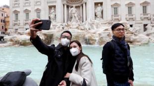 Turistas con máscaras frente a la Fontana di Trevi, el 31 de enero de 2020 en Roma.