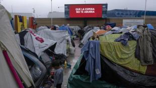 """Un niño migrante se encuentra en un campamento improvisado cerca de una pantalla en la que se lee """"Que la espera no te aburra"""", próximo al del puerto de El Chaparral en Tijuana, estado de Baja California, México, el 11 de marzo de 2021"""
