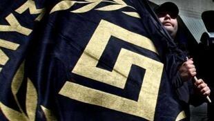 Un militante del partido neonazi Amanecer Dorado sostiene una bandera con el logo de su agrupación, el 21 de abril de 2012 en Atenas.