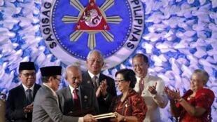 O presidente Benigno Aquino (2° à direita) durante a cerimînia que celebrou o acordo com a guerrilha muçulmana do MILF, nesta quinta-feira (27), em Manila.