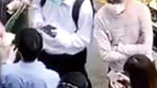 """民主党议员许志峯(背向镜头)及甘乃威(左上角)在警署外向党友筹款保释被捕的郑丽琼,疑有警员在警署内拍下此照,交给亲共政党抹黑许甘两人""""收钱示威""""。"""