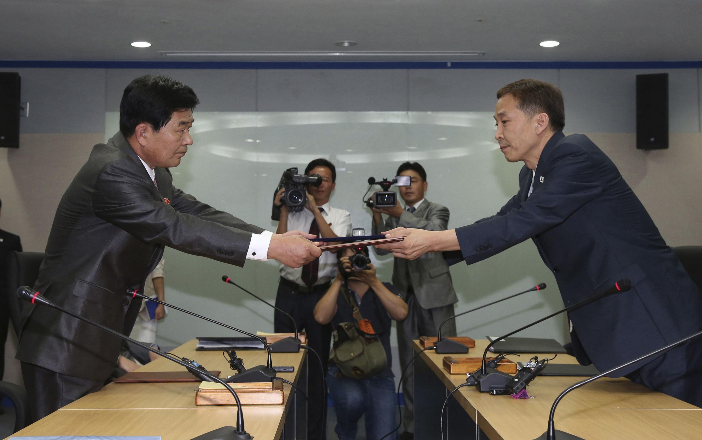 Hai trưởng phái đoàn Nam-Bắc Triều Tiên (Park Chol-su và Kim Ki-Woong) trao cho nhau thỏa thuận mở lại Kaesong - REUTERS