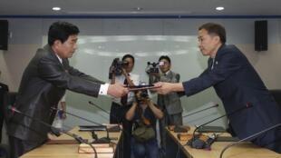 Le chef de la délégation sud-coréenne Kim Ki-Woong (d.) et son homologue nord-coréen Park Chol-su s'échangent l'accord signé, pour la réouverture du parc industriel de Kaesong, le 14 août 2013.