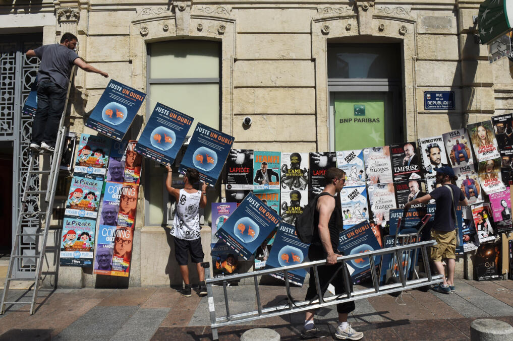 Artists of the Off Festival paste their posters in the streets of Avignon.