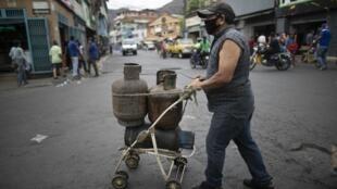 Venezuelano transporta bujões de gás nas ruas de Caracas.
