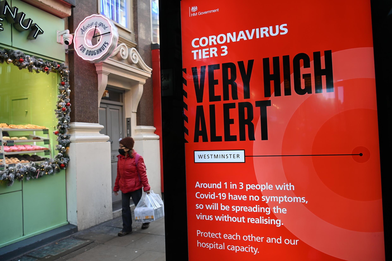 Un peatón pasa por delante de un cartel electrónico con un mensaje del gobierno que muestra el actual nivel de alerta de coronavirus en el centro de Londres, el 17 de diciembre de 2020