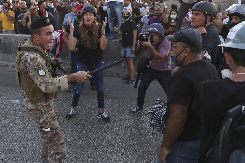 Um soldado libanês ordena manifestantes anti-governo a recuar na manifestação de ontem em Beirute