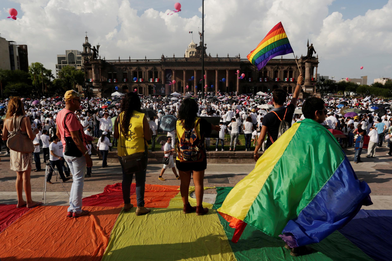 Des Mexicains se tiennent avec des drapeaux multicolores devant des milliers de catholiques et conservateurs réunis contre la légalisation du mariage homosexuel dans la ville de Monterrey, le 10 septembre 2016.