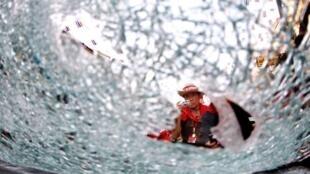 """一位示威者對着在""""紅衫軍""""與政府軍對抗中被子彈打碎的玻璃拍照. (12/4/2010)"""