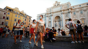 People wearing face masks walk in front of the Trevi Fountain in Rome.