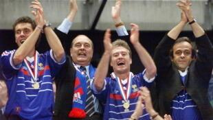 Jacques Chirac, au centre, entouré de Laurent Blanc (à gauche) et de Didier Deschamps et Michel Platini (à droite), lors de la victoire de l'équipe de France de football, en finale de la Coupe du monde 1998.