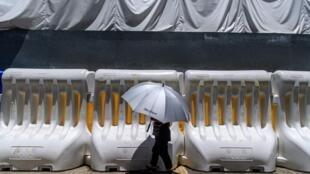 Una transeúnte pasa por delante de unas barreras de seguridad de la policía colocadas en el exterior del Consejo Legislativo de Hong Kong el 30 de junio de 2020, cuando China aprobó la polémica ley de seguridad nacional