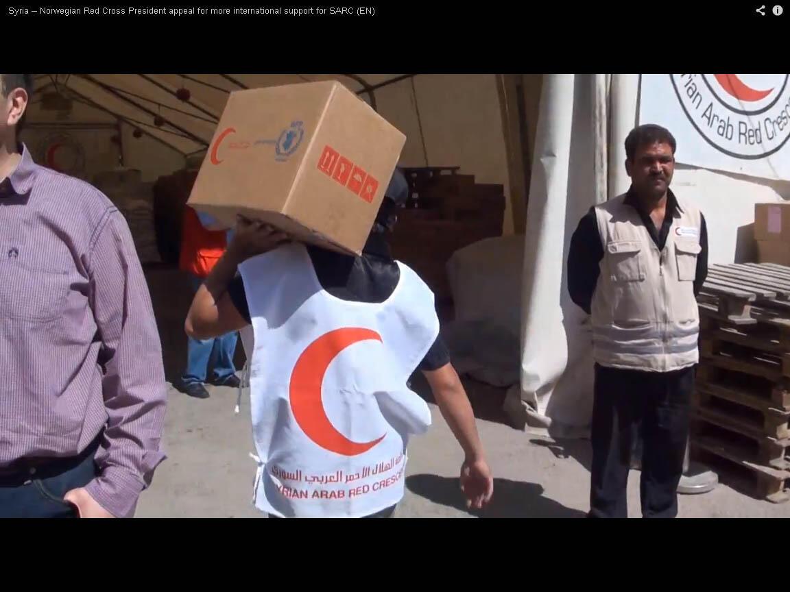 Agente do Crescente Vermelho árabe-sírio distribui caixa com alimentos na Síria.