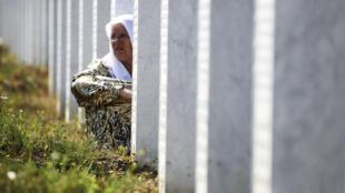 Une musulmane assise près de la pierre tombale d'un proche, au mémorial Potocari, le 11 juillet 2012.