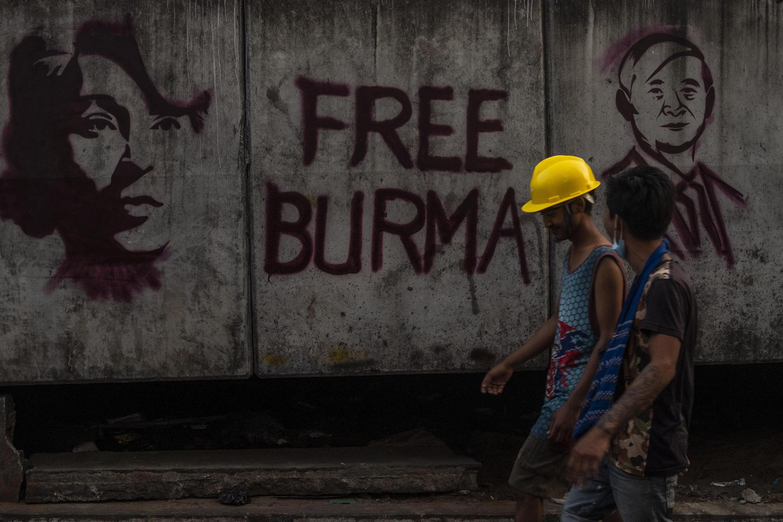 Người biểu tình Miến Điện đi qua bức tường vẽ graffiti tổng thống Win Myint (P) và lãnh đạo Aung San Suu Kyi, tại Rangoon, Miến Điện, ngày 17/03/2021.