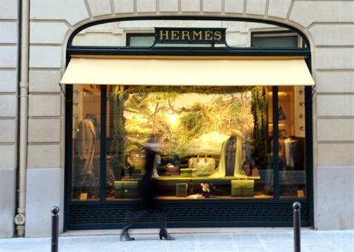 No time to dawdle - a Parisienne walks past a Hermès shop