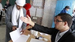 A Tunisian man picks up a ballot paper at a polling station during an election in Sidi Bouzid 23 October, 2011.
