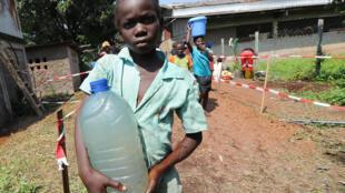 Une jeune fille porte un bidon d'eau, dans le centre Don Bosco de Bangui, qui abrite des milliers de déplacés internes, dont des centaines d'enfants.