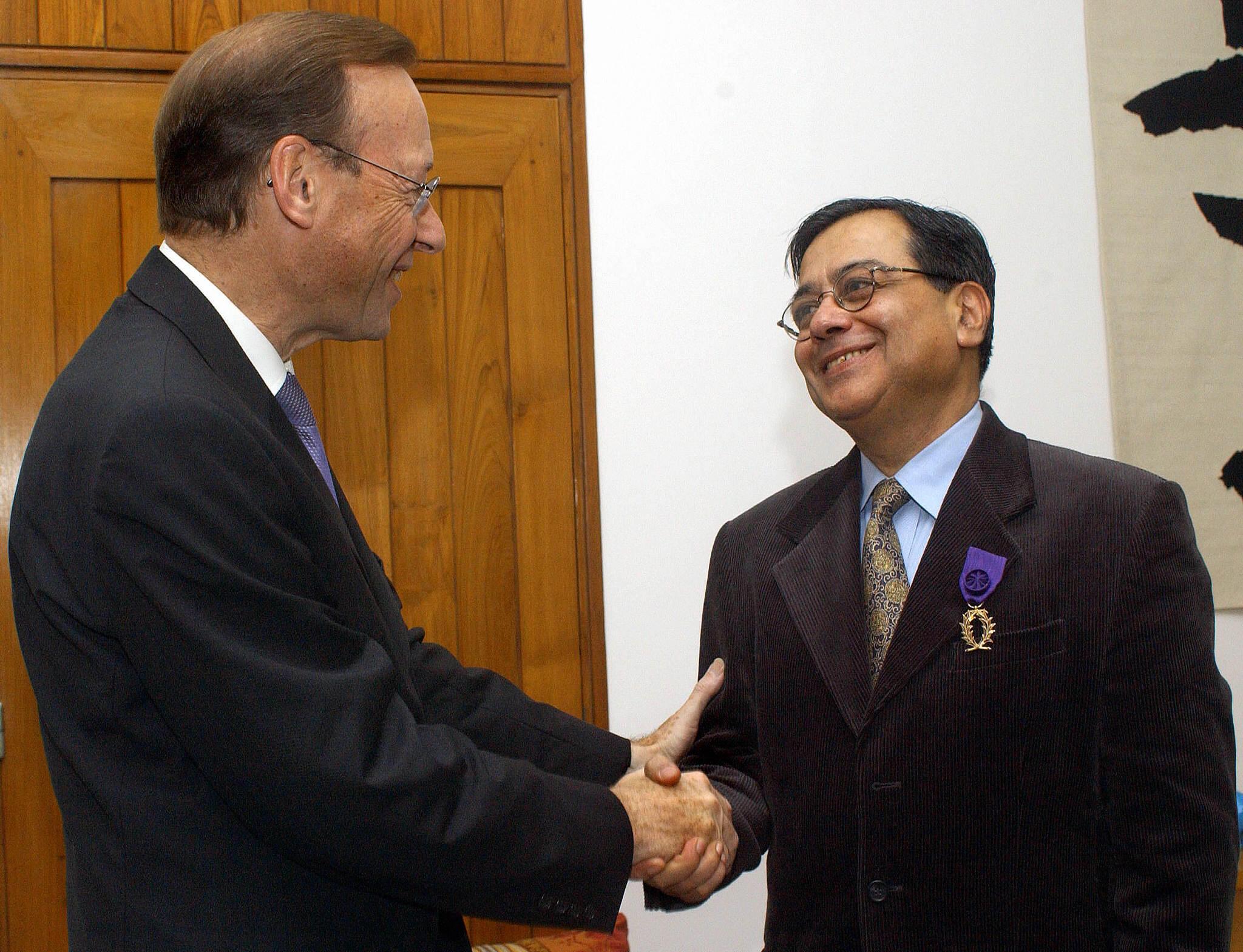 Le ministre français de la Coopération et de la Francophonie, Pierre-André Wiltzer (gauche) félicite le professeur Balveer Arora (droite) après lui avoir remis un prix d'excellence académique à l'ambassade de France à New Delhi, le 10 novembre 2003.