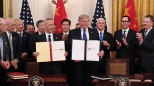 El viceprimer ministro chino Liu he y el presidente de EEUU Donald Trump enseñan el acuerdo comercial firmado en la Casa Blanca, el 15 de enero de 2020