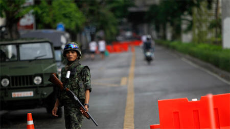 """A soldier mans a military checkpoint outside the barricaded anti-government """"red shirt"""" encampment in Bangkok"""