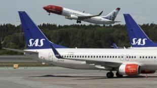 Un appareil de Norwegian Airlines décolle et deux avions de la compagnie SAS au sol, à l'aéroport de Stockholm, le 14 juin 2016 (photo d'illustration).