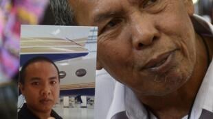 Homem mostra a foto de seu filho, um dos passageiros do voo MH 370 da Malaysia Airlines, desaparecido há dez dias.