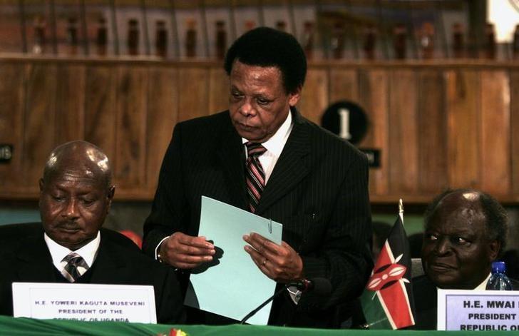 Shugaban kasar Uganda Yoweri Museveni a (bangaren hagu) tare magatakardan kungiyar kasashen gabashin Afrika, Juma Mwapachu (a tsakiya), yayinda suke rattaba hannu kan takardar bayan taron da suka yi a Arusha. 30 ga watan Nuwamba, 2006.